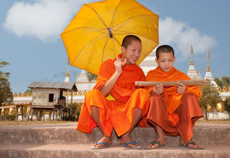 Buddhist monk in Laos while reading old writings Stock Photo