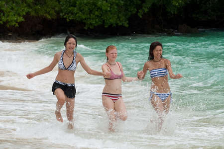 activ: Three girls run on the beach
