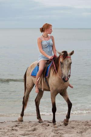 Girl rides on horse photo