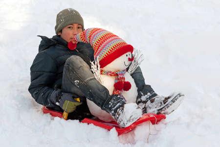 toboga: Ragazzo con lo slittino e il pupazzo di neve Archivio Fotografico