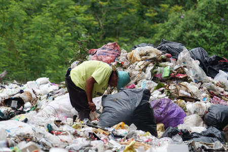 seperation: Penh, Thailand - May 31 2016: Poor people searching on disposal site for useful things to recycle or resell in Northeast of Thailand.