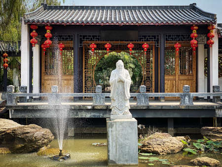 Chinese garden, asian architecture with confucius statue and fountain