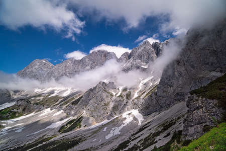 European Alps with clouds, landscape of mountains with snow in summer
