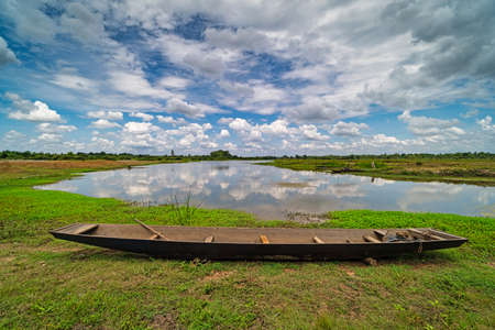 Lake with fishing boat, landscape in summer with cumulus cloud