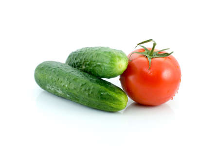 Single tomato and pair of cucumbers isolated on the white background photo
