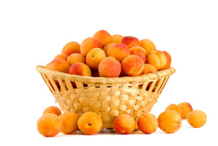 Apricots in a wicker basket isolated on the white background photo