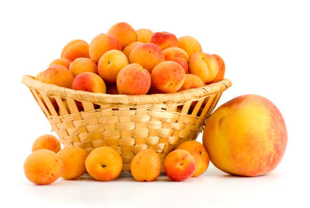 Wicker basket filled with apricots and single peach near isolated on the white background photo