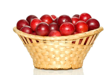 Wicker basket with cherry plums isolated on the white background photo