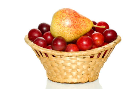 Wicker basket with cherry plums and yellow-red pear isolated on the white background photo