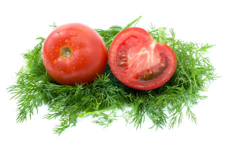 Whole and half of tomato over some dill isolated on the white background photo