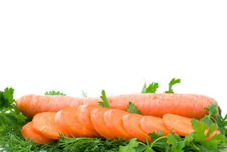 Ripe fresh long carrot and slices over some parsley isolated on the white background (focused on carrot slices) photo