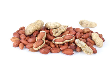 Some whole, shelled roasted peanuts and husk isolated on the white background