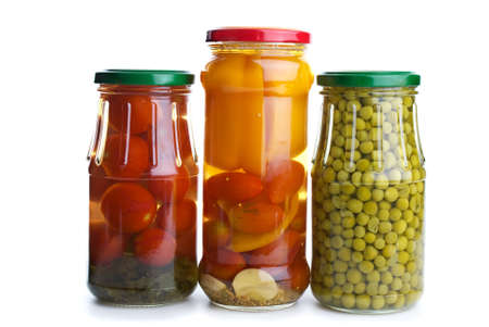 Three glass jars with marinated vegetables (green peas, tomatoes, bell pepper, e.t.c.) isolated on the white background photo
