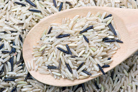 uncultivated: Raw white and black uncultivated rice and wooden spoon (close-up)