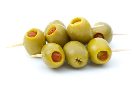 Some olives stuffed with pepper on a wooden toothpicks isolated on the white background