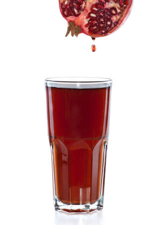 pomegranate juice: Half of pomegranate with drop and glass with juice isolated on the white background