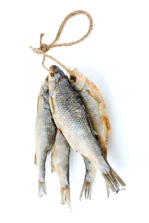 rutilus: Five dried sea roach fishes on the rope isolated on the white background Stock Photo