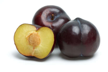Plums (whole and half) isolated on the white background photo