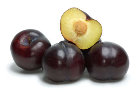 Some whoe plums and one half isolated on the white background photo