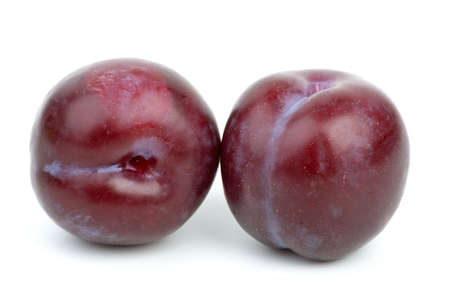 Two violet plums isolated on the white background photo