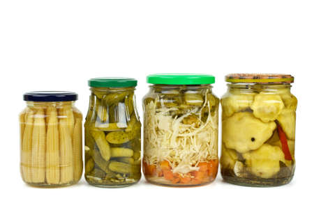 cymbling: Glass jars with marinated vegetables (corn ears, cucumbers, cabbage, carrot  and cymblings). Isolated on white background