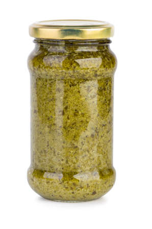 Glass jar with pesto sauce isolated on the white background