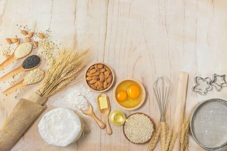 Kitchenware, barley, almond nuts, flour, eggs, butter, bottle of oil, milk and different seeds on wooden background with free text space, top view.