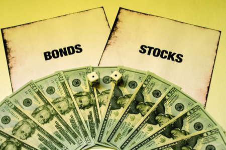 money and dice on stocks and bonds Stok Fotoğraf