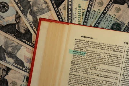 dictionary with economy highlighted with money background Banco de Imagens
