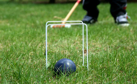 croquet ball and hoops with mallet in background
