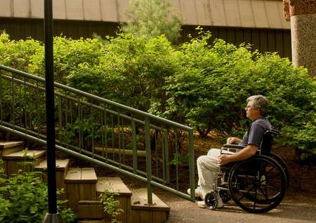 Mann, sitzend in einem Rollstuhl contemplating eine Reihe von Treppen Standard-Bild - 4931714