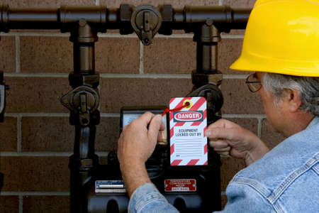 lockout: man attaching lockout tag to a meter Stock Photo