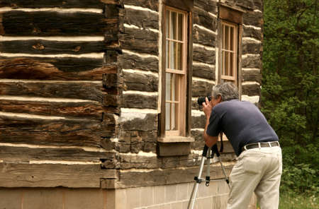 man photographing a rebuilt nineteenth century log cabin Stock Photo - 4931729