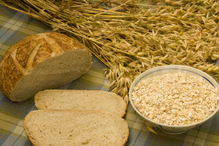 grain bread with oat stalks and a bowl of oatmeal