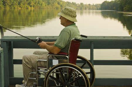 handicap: disabili uomo pesca da una sedia a rotelle accessable dock Archivio Fotografico