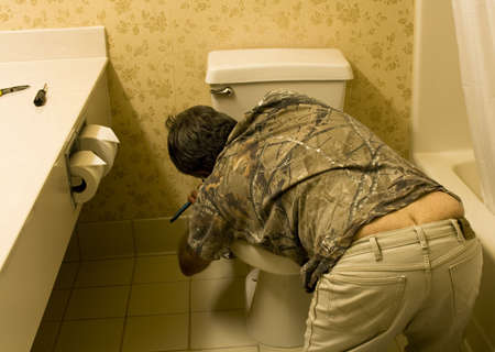 plumber working on a toilet with a slight butt crack showing Stock Photo - 5517821