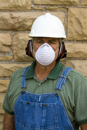 male worker wearing hardhat,ear protection,and dust mask Stock Photo - 5529419