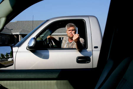 man showing middle finger in anger to another driver photo