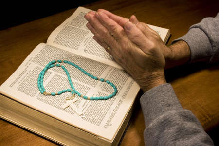 praying hands on a bible with a rosary Stok Fotoğraf