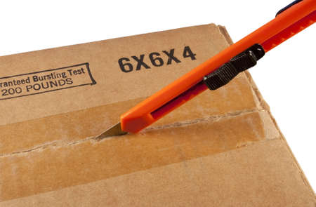 box cutter being used to open a cardboard container Stock Photo