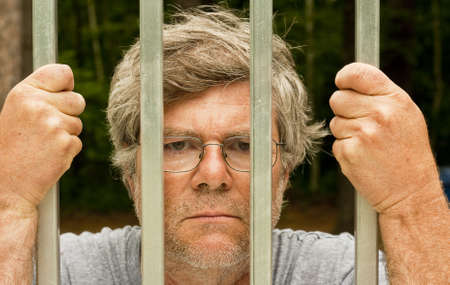 man in prison with hands wrapped around the bars Stock Photo