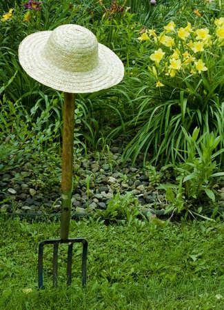 園芸のフォークおよび花の背景と麦わら帽子