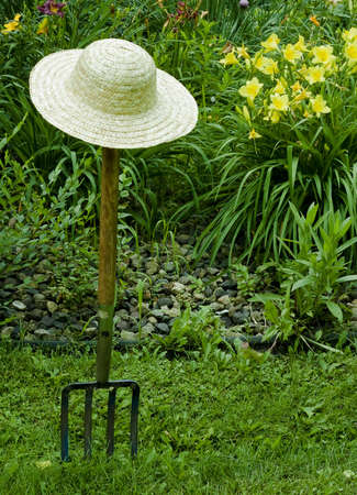 gardening fork and straw hat with a background of flowers Stock Photo - 7316316
