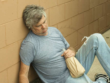 homeless man with his bottle passed out in an alley Stock Photo - 7396485