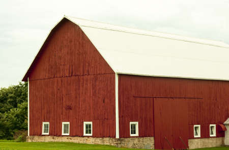 old red family barn with windows on a stone foundation photo