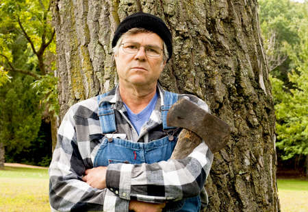 lumberjack holding a double axe posing against a large tree Stock Photo - 7904306