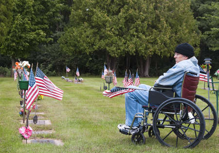 a memorial to fallen soldiers: disabled veteran in a wheelchair at the cemetary remembering his fallen brothers