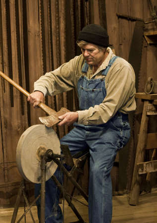 sharpen: man sharpening an axe on an old pedal powered grinding stone