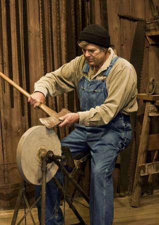 Mann Schärfen der Axt auf eine alte Pedal angetriebene Schleifmaschine stone Standard-Bild - 7988817