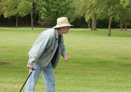 senior man walking in the park with a cane
